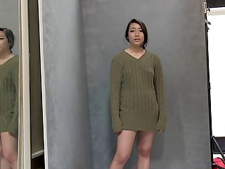 Asian girl in a loose sweater looks sexy posing for pics